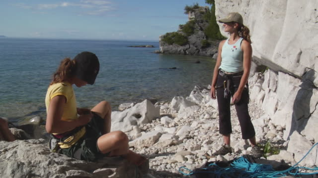 ws two female climbers sitting on beach and preparing gear, lion's head, ontario, canada - baseballmütze stock-videos und b-roll-filmmaterial