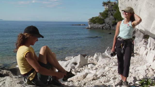 vídeos y material grabado en eventos de stock de ws two female climbers sitting on beach and preparing gear, lion's head, ontario, canada - gorra de béisbol