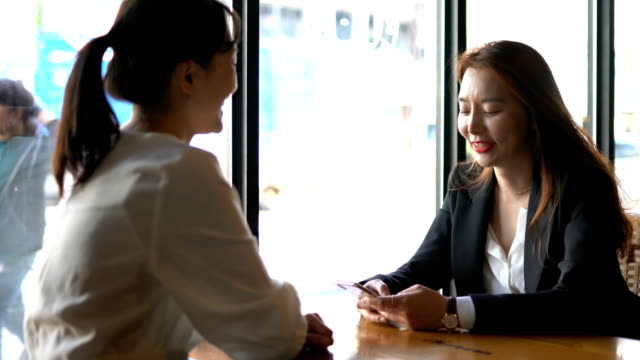 two female colleagues talking in the cafe - korea stock videos & royalty-free footage