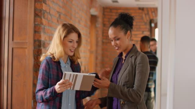 Zwei weibliche Kollegen plaudern und lächelnd in die Startup Büro Flur