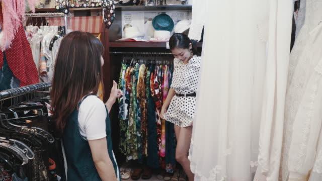 リサイクルショップでヴィンテージ衣類を一緒に買い物する2人の女性客 - 衣料品店点の映像素材/bロール