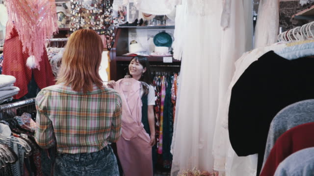 two female customers shopping together for vintage clothing in a thrift store - dress stock videos & royalty-free footage