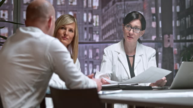 DS Two female doctors in a meeting with a male project leader
