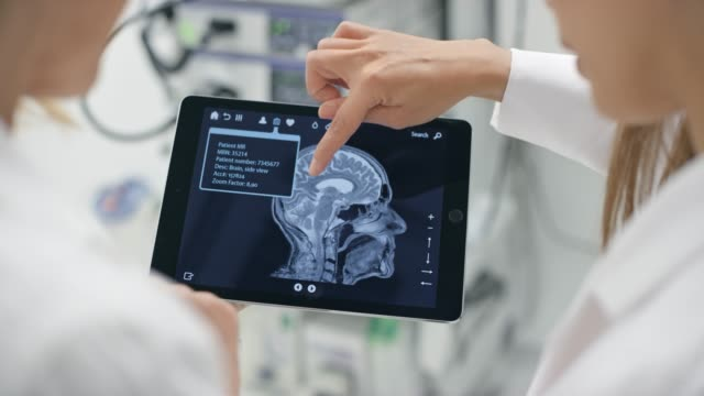 Two female doctors looking at the brain scan show on a digital tablet