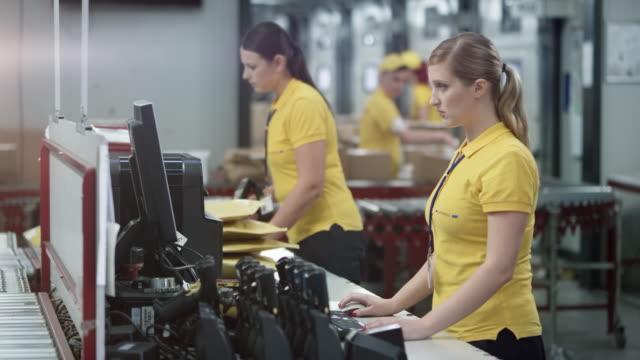 två kvinnliga medarbetare arbetar på datorn och packning kuvert på kontoret skrivbordet i lagret - produktionslinjearbetare bildbanksvideor och videomaterial från bakom kulisserna