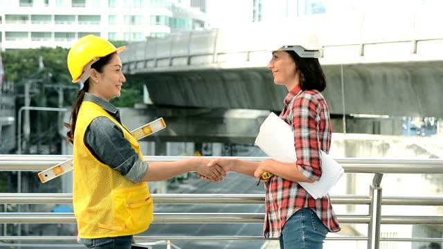 vídeos de stock e filmes b-roll de two female engineers shaking hands on modern city background. - arquiteta