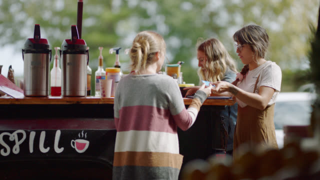 two female entrepreneurs make coffee and run a credit card payment on a tablet - booth stock videos & royalty-free footage