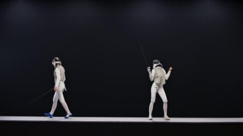 vídeos y material grabado en eventos de stock de slo mo ld dos esgrimistas femeninos durante un partido y uno celebrando ganar un punto - examen