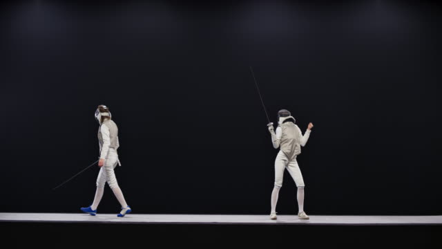 slo mo ld two female fencers during a match and one celebrating winning a point - confrontation stock videos & royalty-free footage
