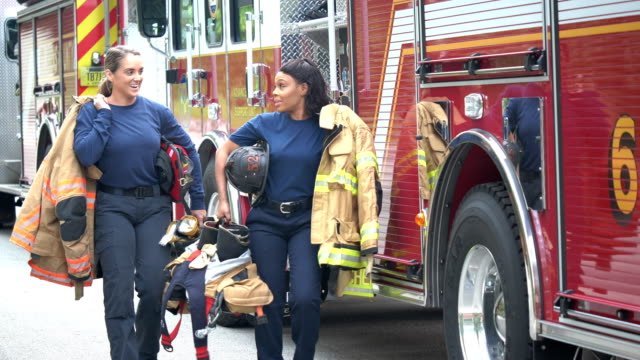 two female firefighters walking next to fire trucks - fire station stock videos & royalty-free footage
