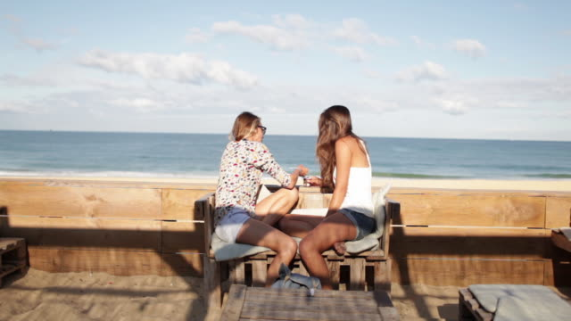 two female friends drinking coffee at bar on the beach in the south of france - floral pattern stock videos & royalty-free footage