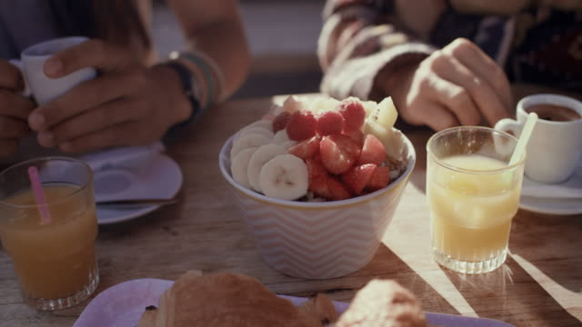 two female friends eating breakfast with fresh fruit and coffee at beach bar by atlantic ocean in the south of france. - frühstück stock-videos und b-roll-filmmaterial
