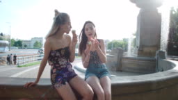 Two female friends eating ice cream in a city.