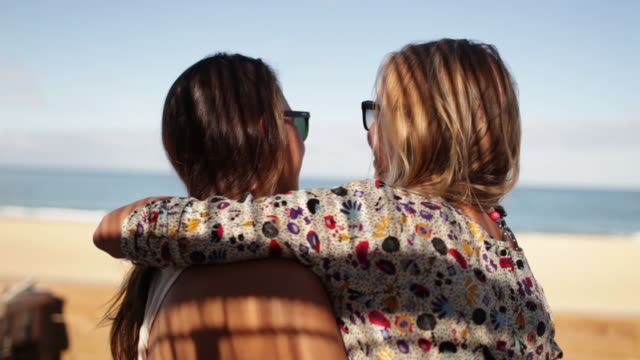 two female friends embracing at bar by the beach in the south of france. - ansikte mot ansikte bildbanksvideor och videomaterial från bakom kulisserna