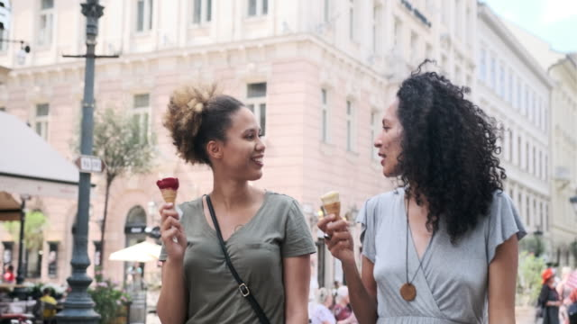 two female friends enjoying ice cream in budapest - city break stock videos & royalty-free footage