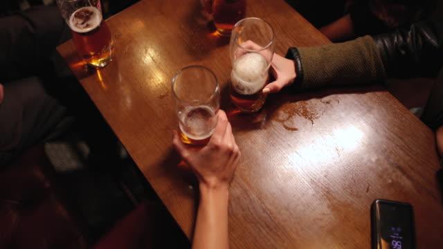 vidéos et rushes de deux amies retenant le verre de bière au pub - alcool