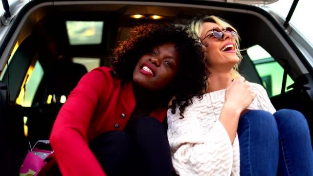 zwei freundinnen in einem offenen kofferraum bei sonnenuntergang - heckklappe teil eines fahrzeugs stock-videos und b-roll-filmmaterial