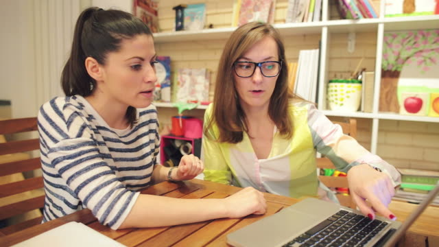 Two female friends in bookstore looking at laptop.