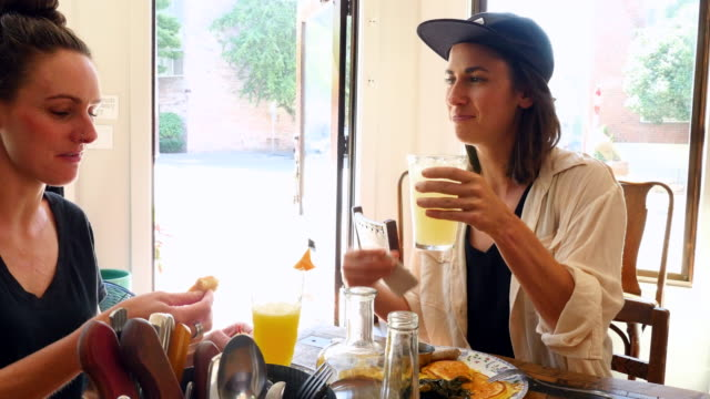 vidéos et rushes de ms two female friends in discussion while sharing lunch in restaurant - tentation