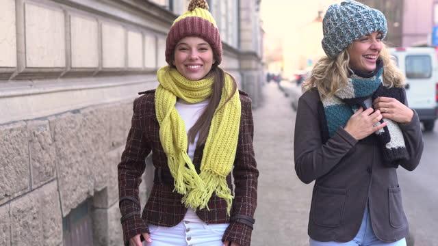 vidéos et rushes de deux amies dans la marche chaude de vêtement d'automne et ayant l'amusement à la ville - représentation féminine