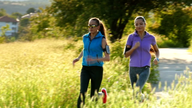 two female friends jogging in the field-slow motion - arm band stock videos & royalty-free footage
