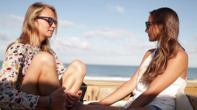 Two female friends laughing, spending time on the beach in the South of France