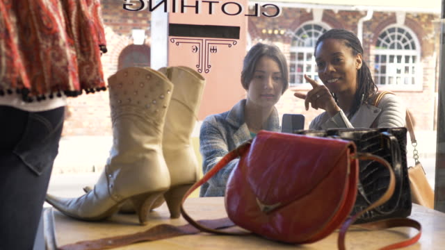 two female friends looking at display in vintage clothes shop window - motivation stock videos & royalty-free footage
