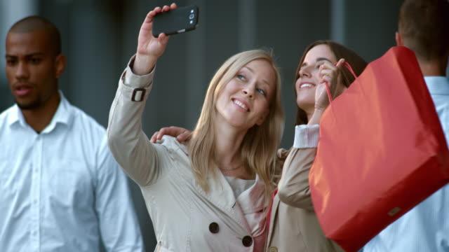 SLO MO two female friends making shopping spree selfies