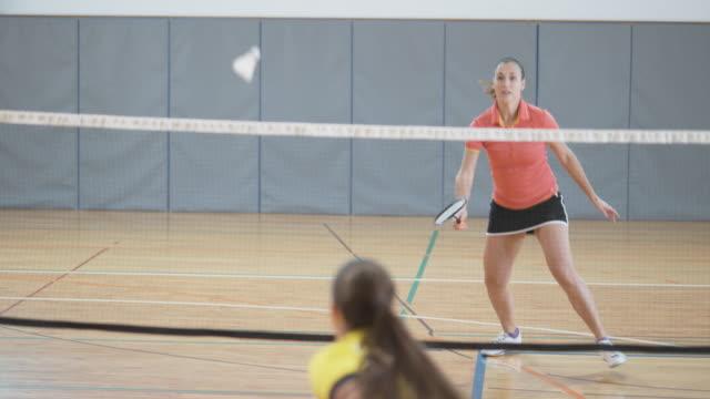 vídeos de stock, filmes e b-roll de duas amigas jogando badminton indoor - badmínton esporte