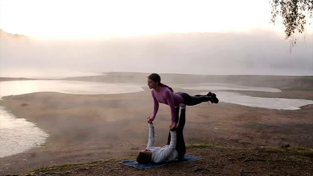 Two female friends practicing yoga at sunrise near the beautiful foggy lake