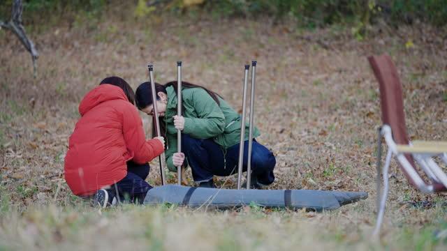 キャンプ場を準備している2人の女性の友人 - ピクニック点の映像素材/bロール