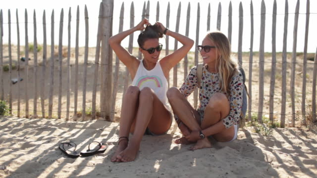 stockvideo's en b-roll-footage met two female friends relaxing on sand dune by the beach in the south of france - in kleermakerszit