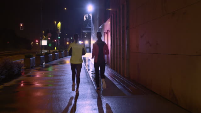 TS Two female friends running on rainy night in city