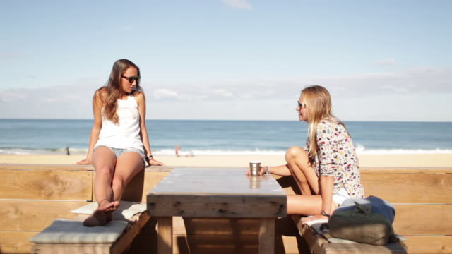 Two female friends sitting, talking at bar by the beach in the South of France.