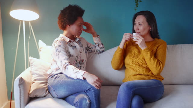 two female friends smiling and drinking coffee at home - female friendship stock videos & royalty-free footage