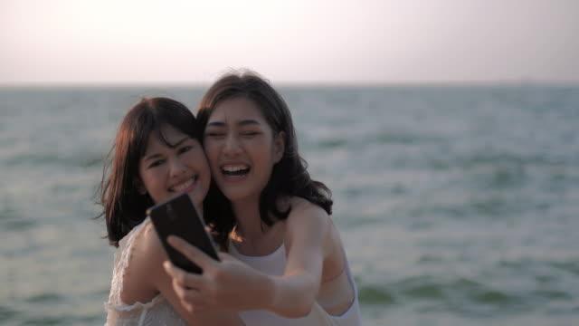2 女性の友人は、携帯電話が付いている浜で、selfie を服用します。lgbt の vacation.lgbt のコンセプトです。 - 撮影テーマ点の映像素材/bロール