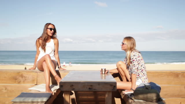 Two female friends talking, laughing at bar by the beach in the South of France.