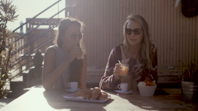 Two female friends talking, laughing, eating breakfast at beach bar by Atlantic ocean in the South of France.