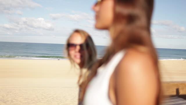vídeos y material grabado en eventos de stock de two female friends talking, standing on the beach in the south of france - sólo mujeres jóvenes