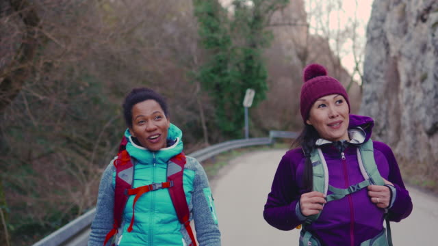 two female friends walking along mountain road - safety harness stock videos & royalty-free footage