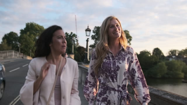 two female friends walking around talking - river thames stock videos & royalty-free footage