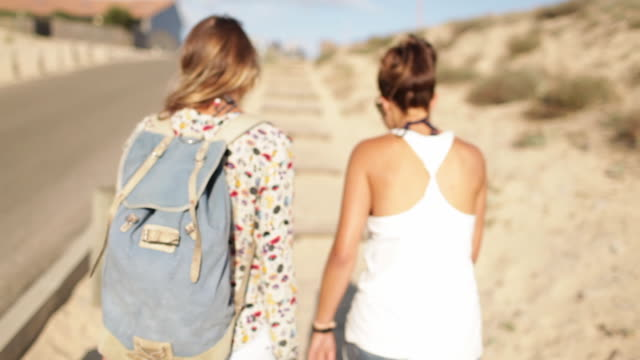 Two female friends walking up sanddune by the beach in the South of France