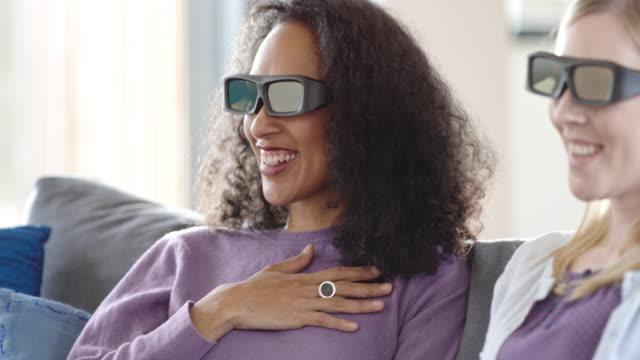 vídeos de stock, filmes e b-roll de duas amigas assistindo tv 3d e se divertindo - óculos de terceira dimensão