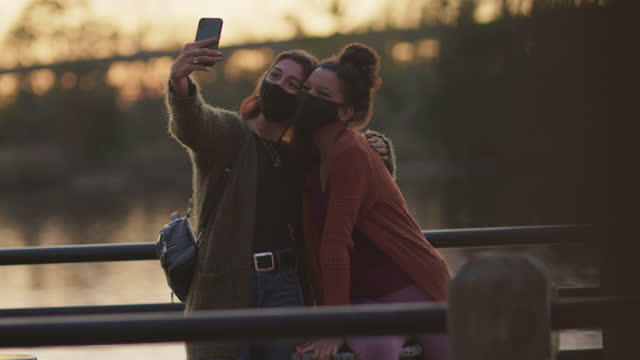 two female friends wearing protective face masks take a selfie together outdoors by the riverside - pedestrian walkway stock videos & royalty-free footage