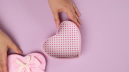 two female hands put on a lilac background a pink cardboard gift box in a heart shape, top view