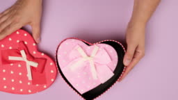 two female hands put on a lilac background a red cardboard gift box in a heart shape