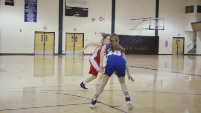Two female high school basketball players competing against each other 1 on 1 during a game