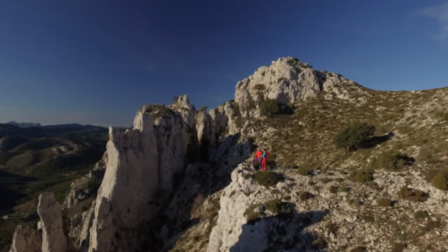 vídeos de stock e filmes b-roll de two female hiker on edge of cliff overlooking mountains surrounded - alicante