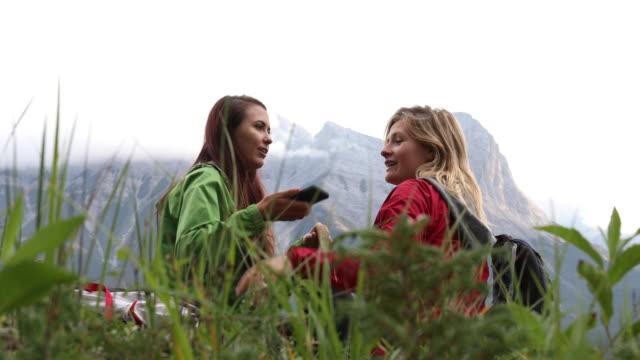vídeos y material grabado en eventos de stock de dos excursionistas mujer relajarse en camino de cresta ridge, nublado el día - sólo mujeres jóvenes