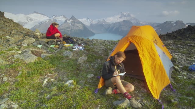 ws two female hikers sitting by their tents on top of mountain, garibaldi provincial park, squamish, british columbia, canada - garibaldi park stock videos & royalty-free footage